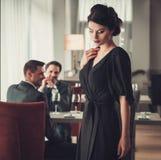 Signora castana elegante in vestito da sera nero in ristorante fotografia stock