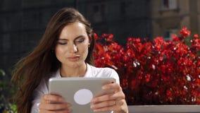 Signora castana lavora con la compressa mentre si siede nel ristorante prima dei fiori rossi video d archivio