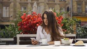 Signora castana legge qualcosa in suo telefono mentre si siede nel ristorante prima dei fiori rossi archivi video