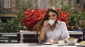 Signora castana legge qualcosa in suo telefono mentre si siede nel ristorante prima dei fiori rossi video d archivio
