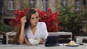 Signora castana mangia l'insalata e guarda qualcosa sulla sua compressa mentre si siede nel ristorante prima dei fiori rossi archivi video