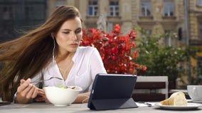 Signora castana mangia l'insalata e guarda qualcosa sulla sua compressa mentre si siede nel ristorante prima dei fiori rossi video d archivio