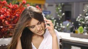 Signora castana parla sul suo telefono mentre si siede nel ristorante prima dei fiori rossi video d archivio