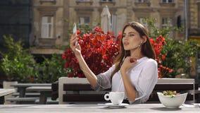 Signora castana parla sul suo telefono tramite cuffie mentre si siede nel ristorante prima dei fiori rossi video d archivio