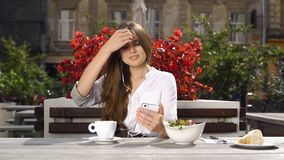 Signora castana parla sul suo telefono tramite cuffie mentre si siede nel ristorante prima dei fiori rossi archivi video