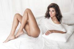 Signora castana sensuale che posa a letto Immagini Stock