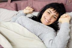 Signora castana sorridente felice che sveglia a letto Fotografie Stock