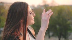Signora castana splendida che gode del sorridere di tramonto stock footage