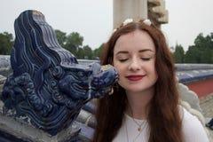 Signora caucasica castana pacifica con la scultura cinese del drago immagine stock libera da diritti