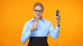 Signora caucasica di affari che mostra i pollici sulla tenuta della mano dello smartphone, applicazione archivi video