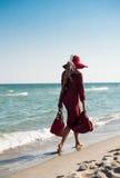 Signora che cammina lungo la spiaggia fotografie stock libere da diritti