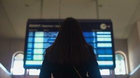 Signora che considera programma sulla stazione ferroviaria, viaggio di pianificazione, treno aspettante video d archivio