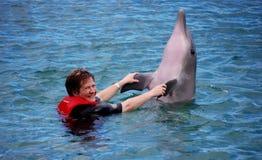 Signora che gode del suo incontro con un delfino Immagine Stock