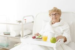 Signora che mangia mela all'ospedale Fotografia Stock Libera da Diritti