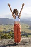 Signora che si leva in piedi sulla parte superiore della montagna Fotografia Stock