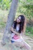 Signora che si siede sotto l'albero che indossa una camicia bianca e gli shorts Fotografia Stock