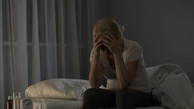 Signora che si siede sul letto, incapace di cadere addormentato dovuto l'emicrania ed il dolore severi di Male archivi video