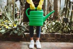 Signora che sta nella serra vicino alle piante con il vaso di versamento Fotografie Stock