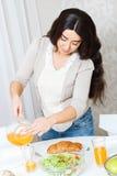 Signora che versa fuori succo d'arancia fotografie stock libere da diritti