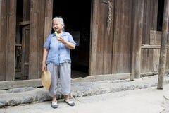 Signora cinese anziana Eating Cucumber Immagini Stock