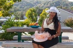 Signora con due cappelli, tè e frutti fotografie stock