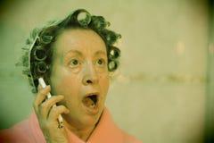Signora con i bigodini sorpresa sul telefono fotografia stock libera da diritti