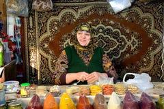 Signora con i denti dell'oro che vendono le spezie davanti a tappeto al mercato a Bacu, capitale dell'Azerbaigian Fotografie Stock