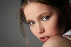 Signora con i grandi occhi che esamina la macchina fotografica Fine in su Fondo grigio Fotografie Stock