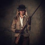 Signora con il fucile da caccia ed il cappello dall'ovest selvaggio su fondo scuro fotografia stock