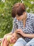 Signora con il gioco del bambino all'aperto Il bello ragazzo ha messo la testa sulle ginocchia della madre fotografia stock libera da diritti