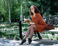 Signora con il libro sul banco di sosta Fotografia Stock