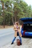 Signora con la vecchia valigia che viaggia sul tronco di automobile blu aperto della strada vicino Fotografia Stock Libera da Diritti