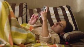 Signora con lo smartphone sul letto