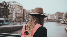 Signora con lo zaino rosso sta sul ponte del fiume Ragazza in cappello alla moda con capelli lunghi e un'attesa del telefono 4K a video d archivio