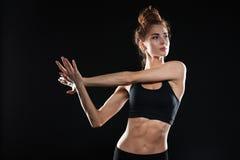 Signora concentrata di sport dei giovani fa l'allungamento degli esercizi Immagine Stock
