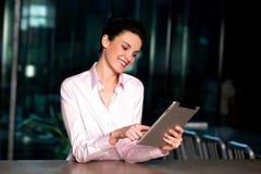 Signora corporativa che fa funzionare il nuovo dispositivo della compressa Fotografia Stock