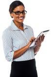 Signora corporativa che per mezzo del dispositivo di cuscinetto di tocco Immagini Stock