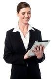 Signora corporativa che per mezzo di un dispositivo della compressa Immagini Stock Libere da Diritti