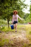 Signora dell'agricoltore con un secchio in un frutteto Fotografia Stock