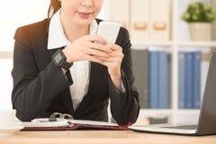 Signora dell'ufficio che per mezzo del telefono cellulare che gioca gioco online fotografia stock libera da diritti