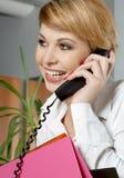 Signora dell'ufficio con le cartelle che fanno una telefonata Fotografia Stock