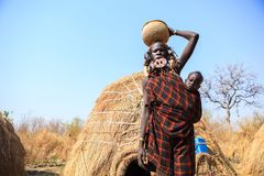 Signora della tribù di Mursi che porta il suo bambino fotografia stock