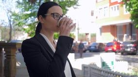 Signora demoralizzata di affari in occhiali che beve caffè sulla via e che pensa a qualcosa video d archivio