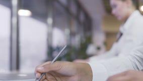 Signora di affari che fa le note sul grafico, eliminante gli occhiali e lasciante posto di lavoro stock footage