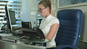 Signora di affari che scrive sul computer portatile all'ufficio stock footage