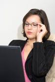 Signora di affari con un computer portatile che tocca i suoi vetri Fotografia Stock