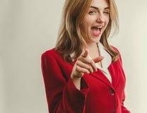 Signora di affari in rivestimento rosso che indica dito in avanti Immagine Stock