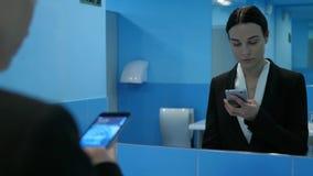 Signora di affari in toilette pubblica ha frustrato gli sguardi a se stessa in specchio ed utilizza lo smartphone moderno video d archivio