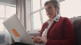Signora di anziano in cuffie facendo uso del suo computer portatile moderno stock footage