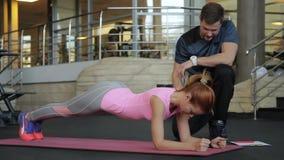 Signora di forma fisica che fa esercizio della plancia con l'istruttore in società polisportiva archivi video
